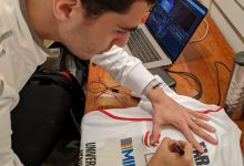 Ali Farag signs a shirt for the World Squash Day auction