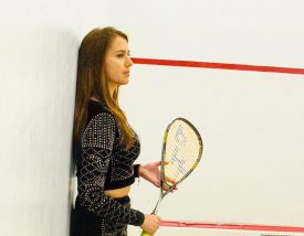 Catalina Pelaez leans against the squash court with her racket in hand
